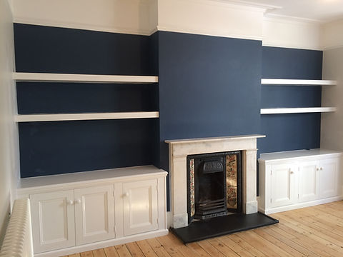 built-in chunky, floating shelves and three door alcove cupboards either side of fireplace