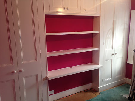 built-in pair of wardrobes with high cupboards and shelving between them across firebreast