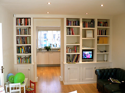 built in cupboard and bookcase unit either side of doorway from lounge to kitchen, chunky shelves above a three door cupboard and a single door cupboard