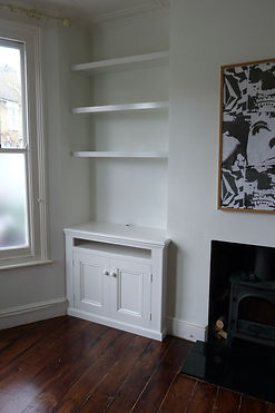 built-in alcove cupboard with media slot above doors and floating shelves above