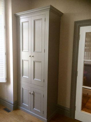 built-in coat wardrobe and shoe cabinet with two tall doors at the top and two small doors below