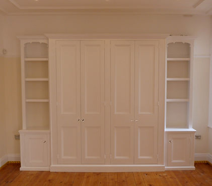 built-in breakfront 4 door wardrobe with single alcove cupboards and decorative bookcases on either side