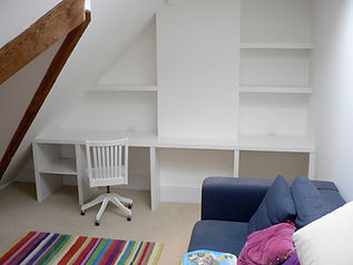 built-in painted desk and chunky floating shelves under-eaves in attic room