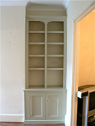 built-in alcove cupboard and split bookcase with decorative scrolls
