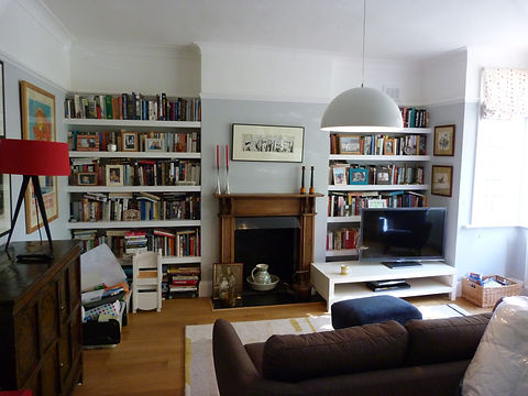 built-in chunky, floating shelves in alcoves either side of fireplace