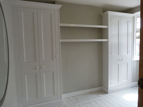 built-in pair of 2 door wardrobes in alcoves with shelves across  firebreast