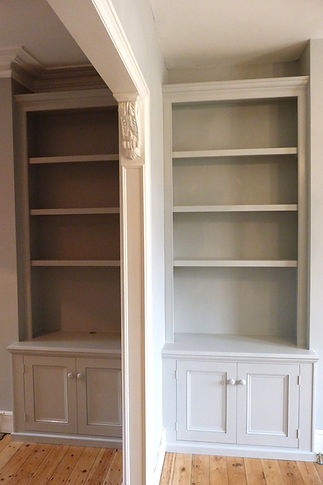 built-in painted pair of two door alcove cupboards and bookcases either side of column