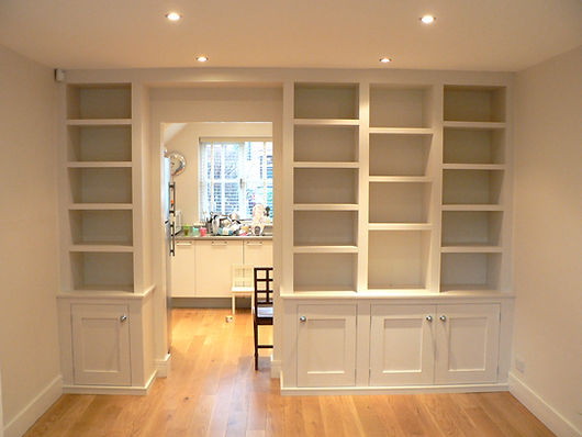 built-in wall to wall shelving unit, modern cubbyhole shelves around doorway with Shaker style cupboards at base