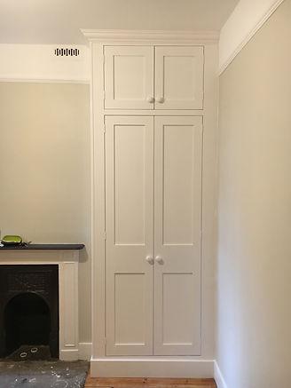 built-in floor to ceiling 1930's style wardrobe, two small top door with two tall doors below