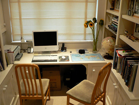 built-in office desk with surrounding library shelves and study storage cupboards