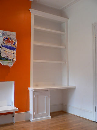 built-in desk, single door cupboard and bookcase in alcove