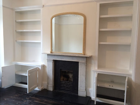 built-in pair of alcove cupboards with doors open to show interior shelving and bookcases above