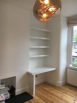 built-in desk and floating shelves in alcove