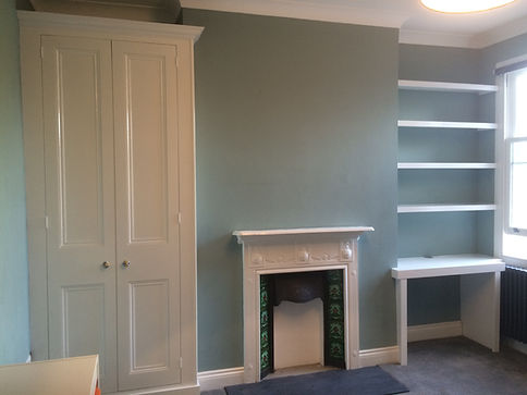 built-in desk and floating shelves in alcove with two door wardrobe in other alcove