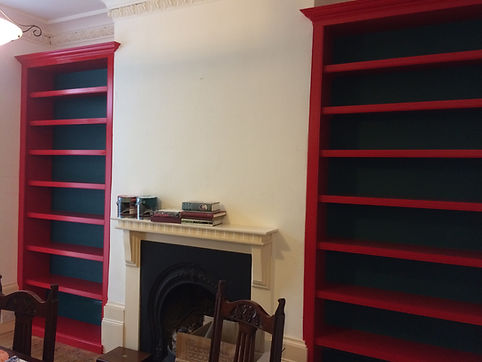 built-in pair of decorative alcove bookcases either side of fireplace