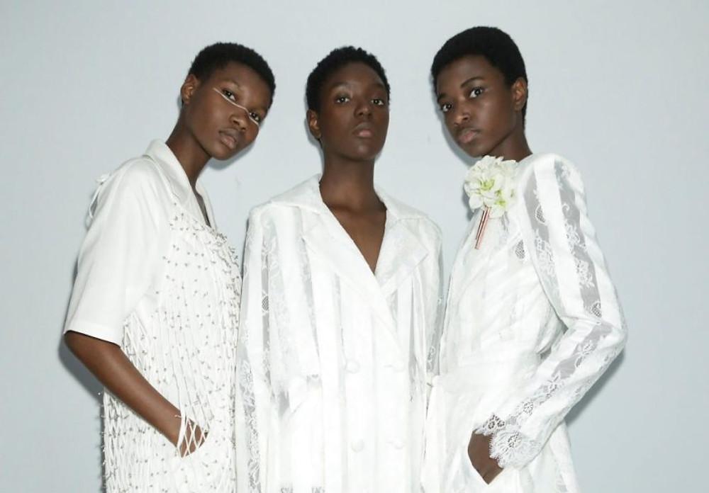 Três mulheres posando de roupas brancas