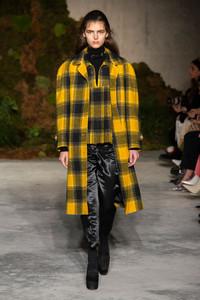 Modelo usando casaco xadrez amarelo
