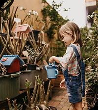 crianca-regando-flores-de-macacao-jeans