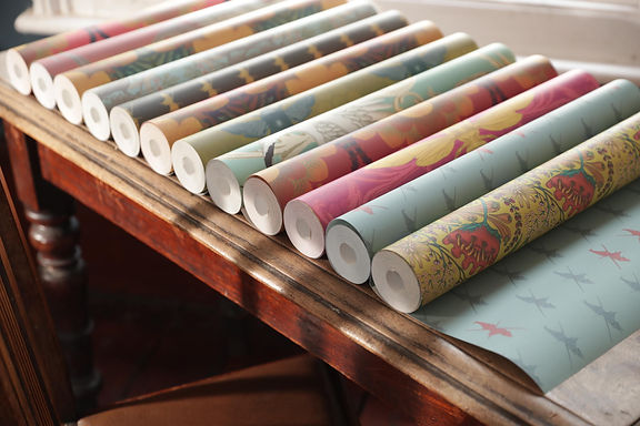 Many rolls of wallpaper in a line cover a vintage wooden table. Different patterns and colours.