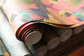 A beautiful photograph of rolls of wallpaper.  one paper lays on top creating a gentle loose swirl