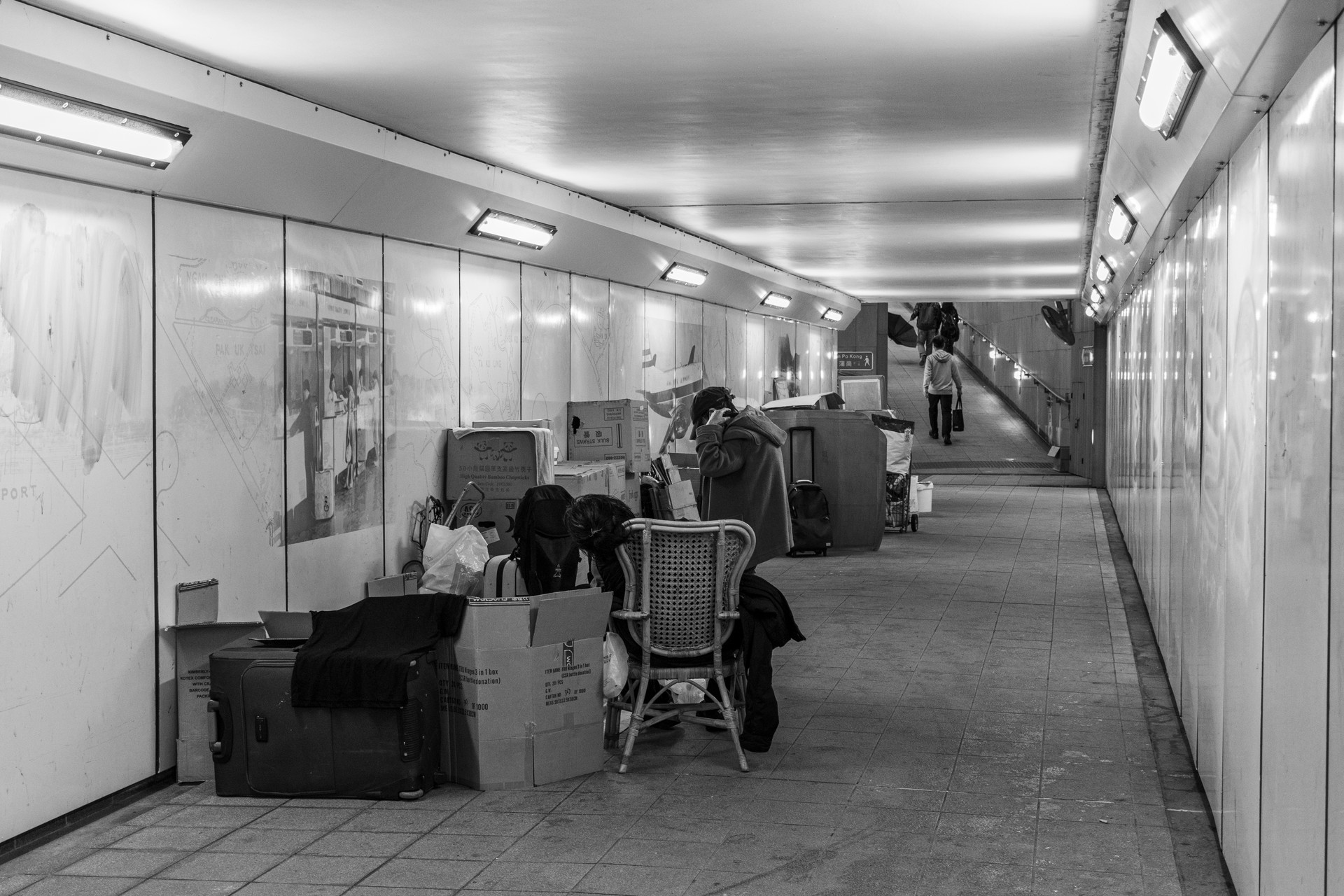 However, some users of the tunnels are living here. In the foreground, homeless people establish their shelter, in contrast, some people are going home by leaving the tunnel in the background.