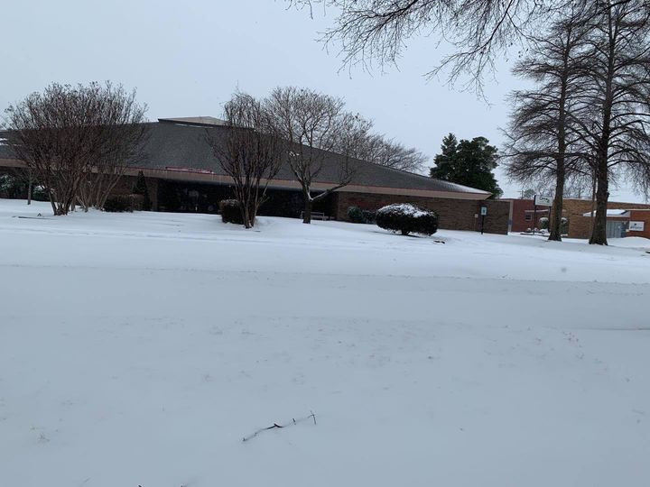 Snow scape of the Blytheville Public Library; building and parking lot are covered in white from the recent snow storm