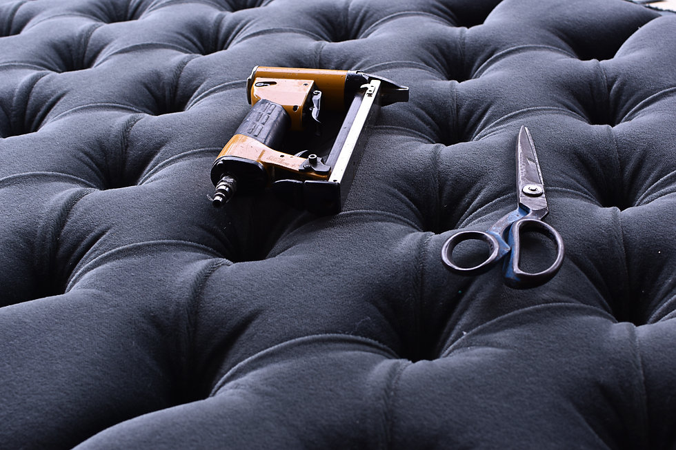 tools on the upholstery of a grey capitoned headboard.jpg