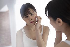 困った顔で鏡を見る女性