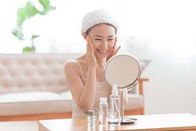 鏡とスキンケアをする女性