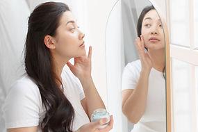 鏡に向かって美容液をつける女性