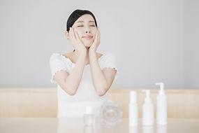 スキンケア商品と両手で顔を触る女性