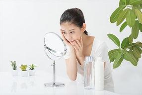 鏡を見ながら肌の手入れをする女性