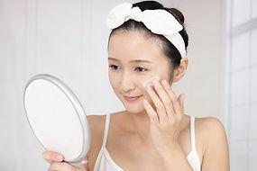 鏡を見ながら保湿クリームを塗る女性