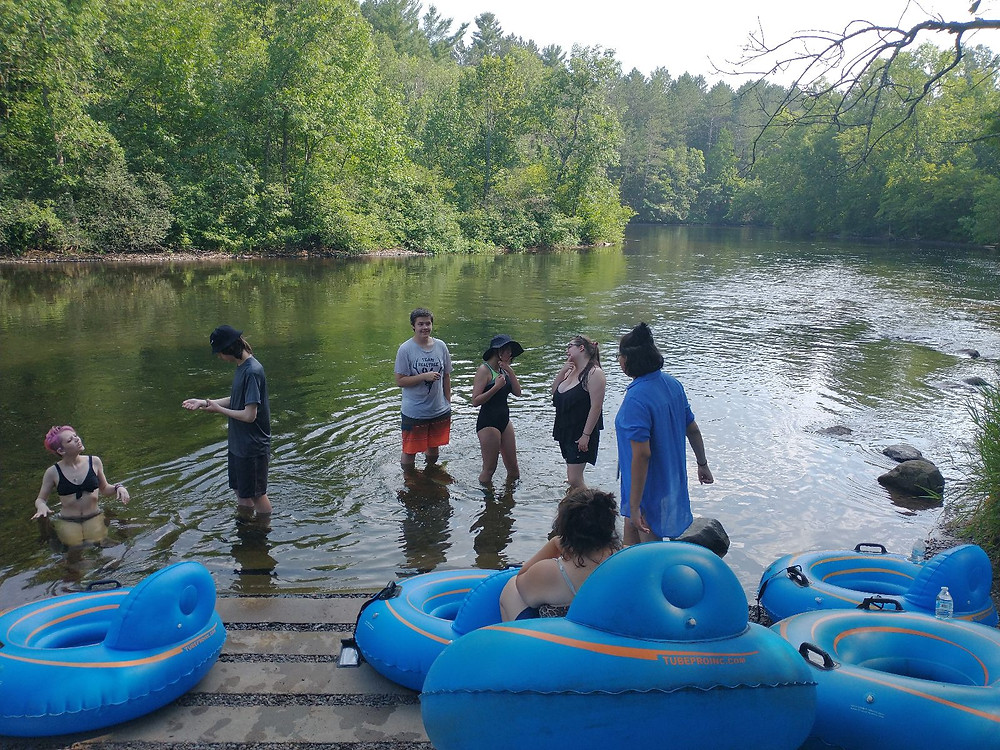 A group of people sitting in inner tubes and standing in a lake