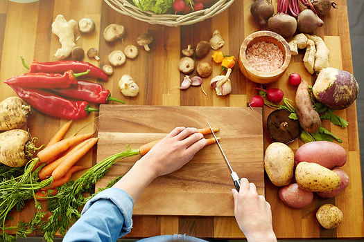 Aerial view of a person chopping carrots on a cutting board, surrounded by other vegetables on the table