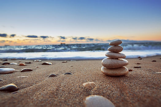 A balanced stack of small, smooth stones sits on the beach near the waves