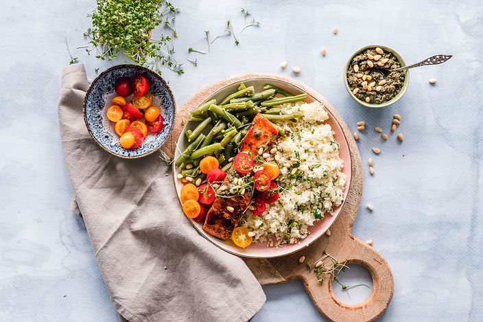 Aerial view of a plate with green beans, sliced grape tomatoes, salmon, and white rice with spices