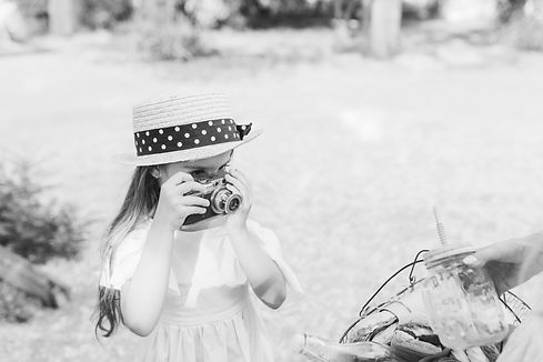 portrait-of-serious-child-with-camera-wears-trendy-boater-hat-decorated-with-black-ribbon-