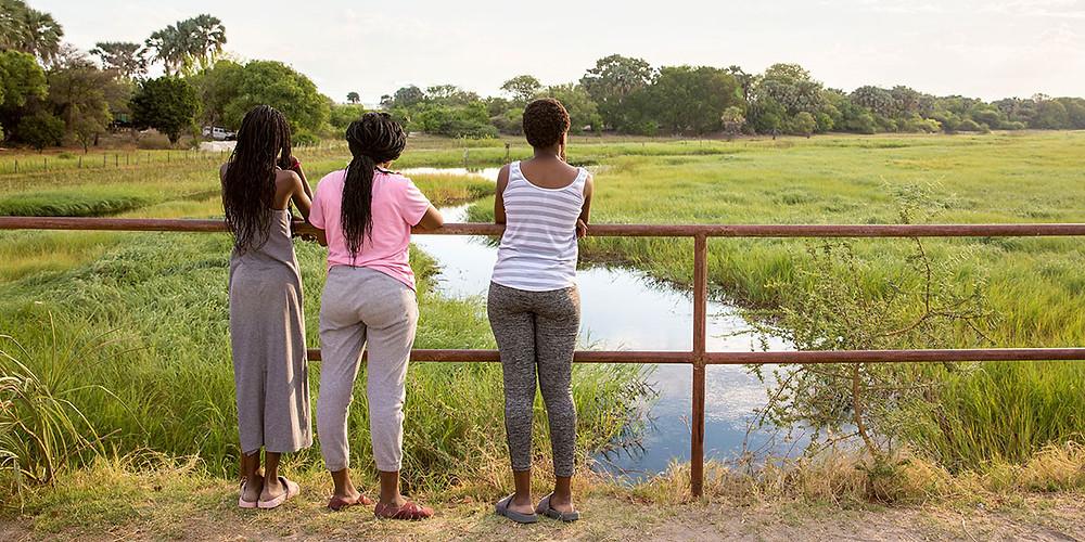 local girls watching okavango delta sunset in Botswana