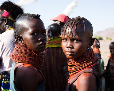 two young kenya girls wearing beads and paint