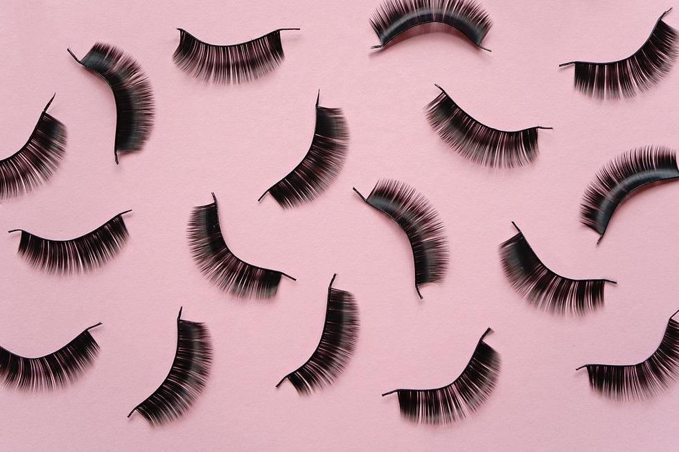 Black false lashes strips on pink backgr