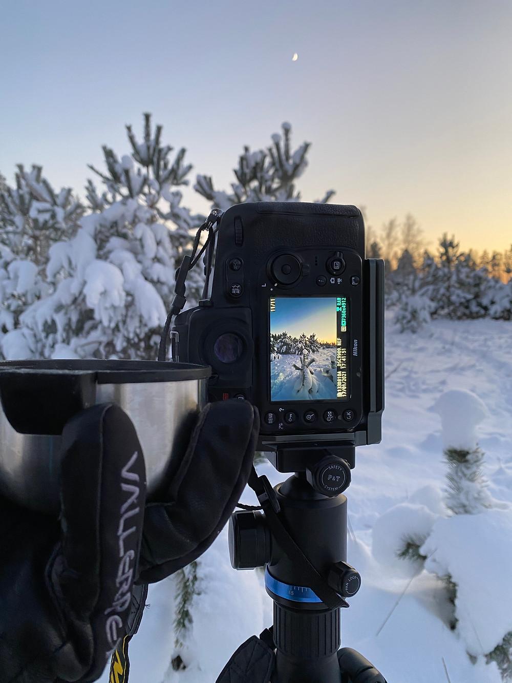 Nikon camera on a tripod shooting winter landscape while having a tea