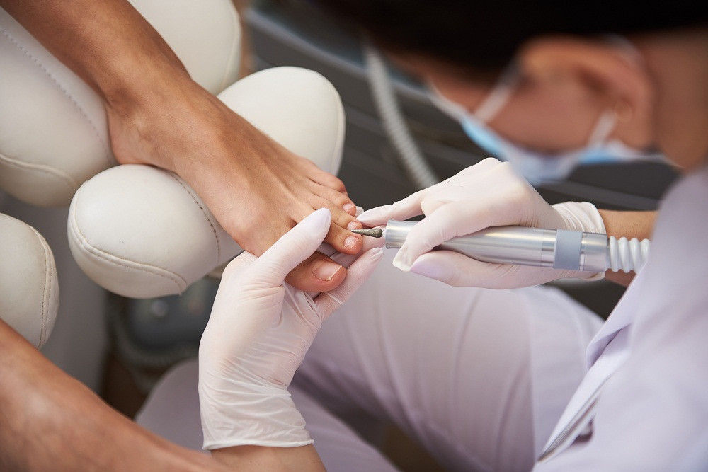 Nail tech performing pedicure