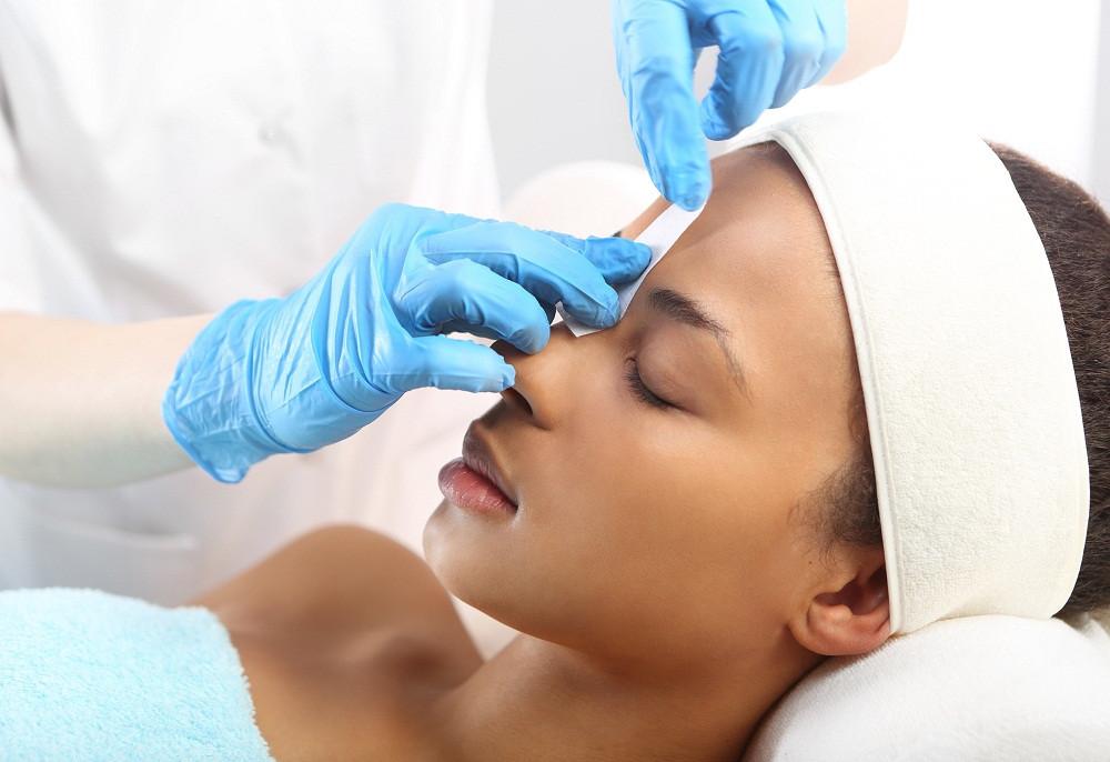 Esthetician performing eyebrow wax