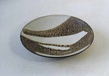 Oxidised stoneware bowl. Thrown and turned. Dark reactive leopard skin spotted outside, inside splash design with white areas. Dark edge to rim