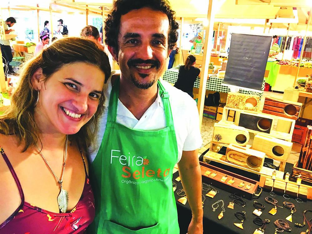 A idealizadora da  feira, Flávia Fagundes  com o expositor  Rodrigo Castro,  do Atelier Pau-Brasil  e as caixas acústicas  de madeira ao fundo