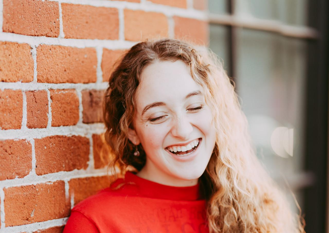 High school senior girl in her high school mascot t-shirt leaning against a brick wall.