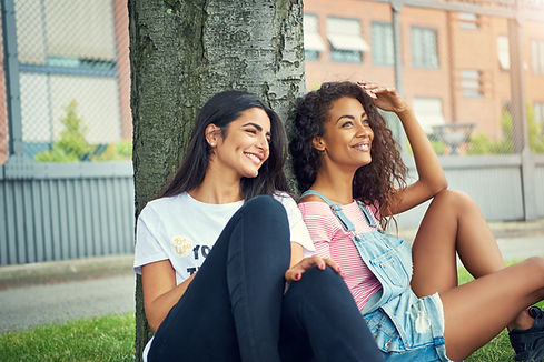 diverse-pair-of-cute-women-sitting-under