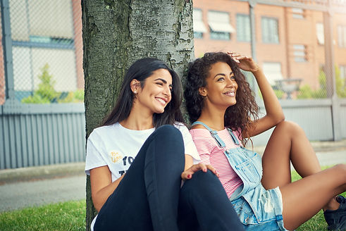 diverse-pair-of-cute-women-sitting-under