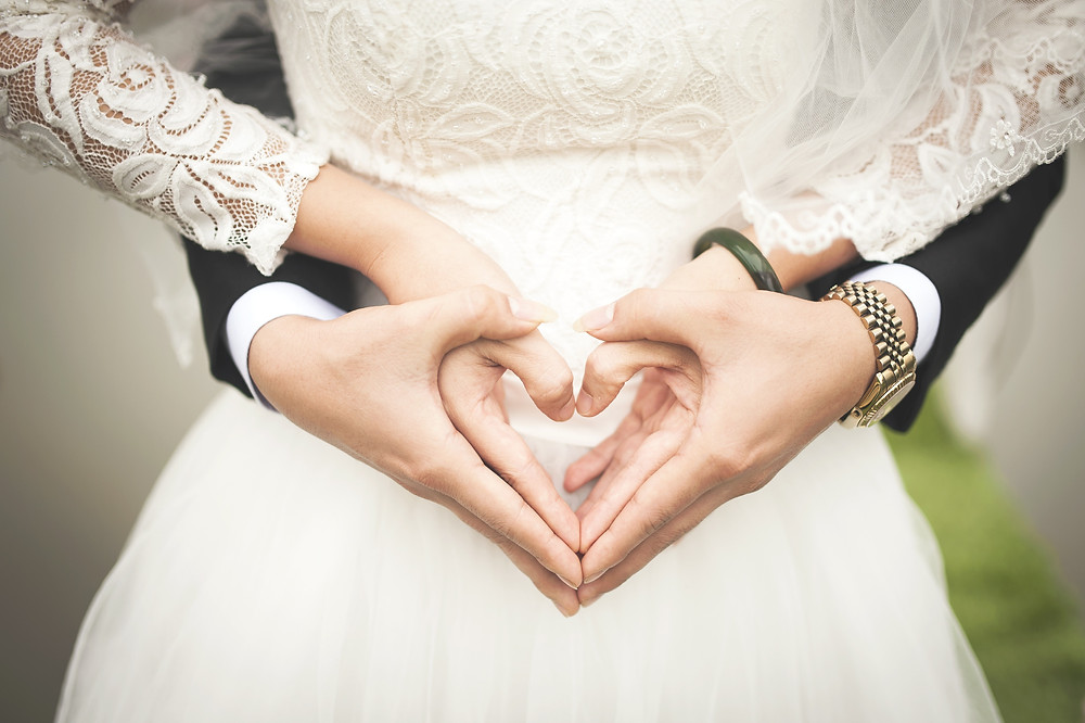 A cover image for an Amazon Book Review blog for Nora Robert's best selling book series. The picture depicts a newly wed couple making a heart sign with their hands over the brides beautiful wedding dress.